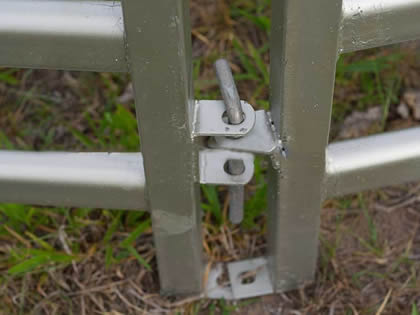 A pin is connecting two cattle corral fence.